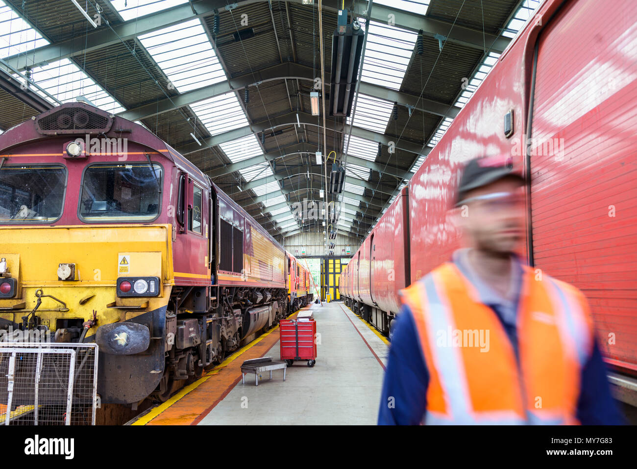 Engineer walking on platform in train engineering factory - Stock Image