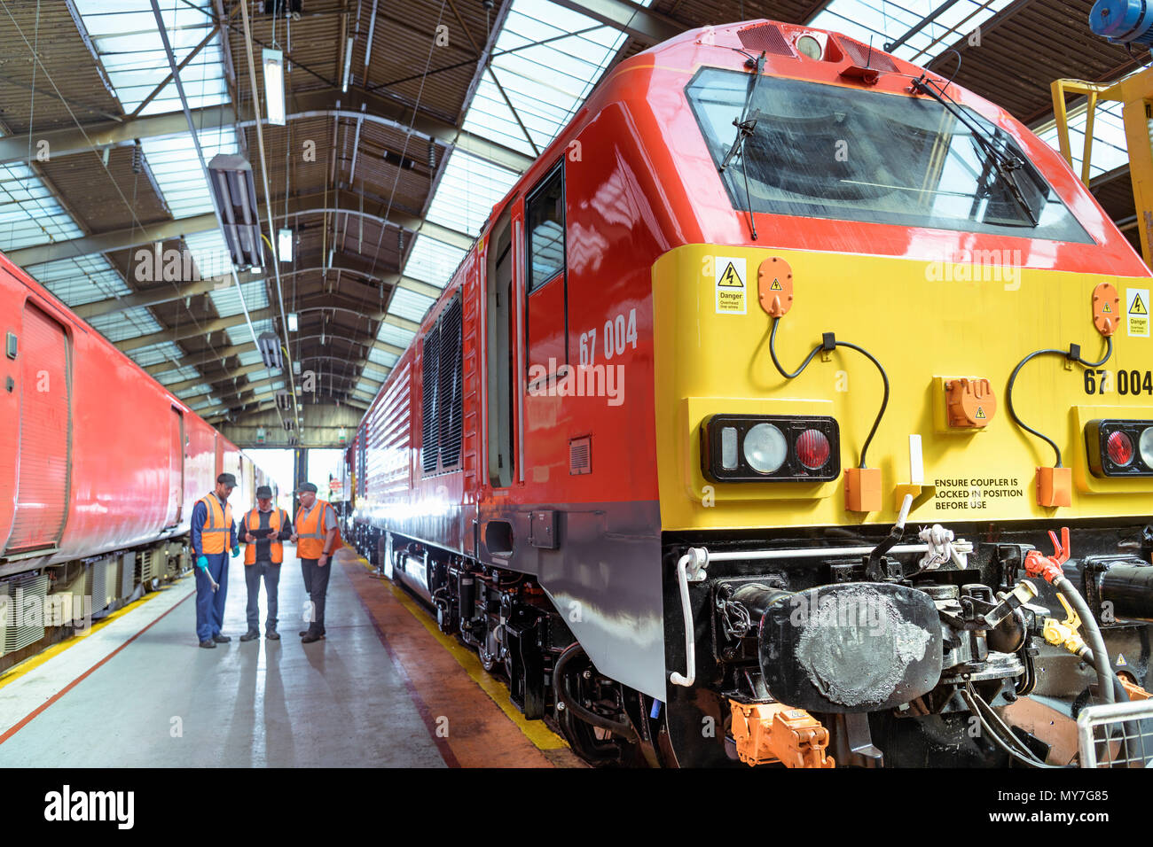 Engineers in discussion next to refurbished locomotive in train engineering factory - Stock Image