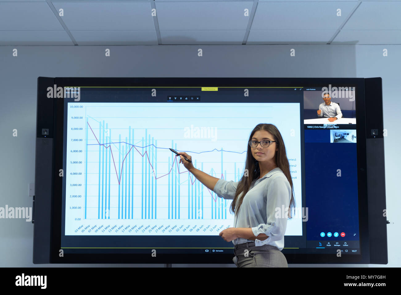 Woman presenting business meeting with graph and video conferencing - Stock Image