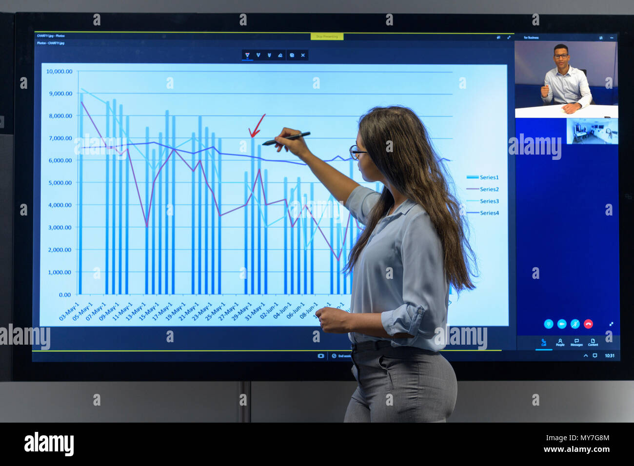 Woman drawing on graph in business meeting with video conference - Stock Image