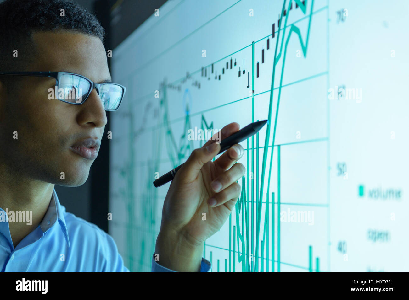 Businessman studying graphs on an interactive screen in business meeting, close up - Stock Image
