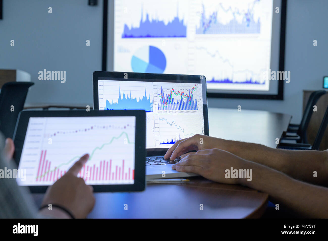Businessman and woman using screens with graphs and charts in business meeting, close up - Stock Image