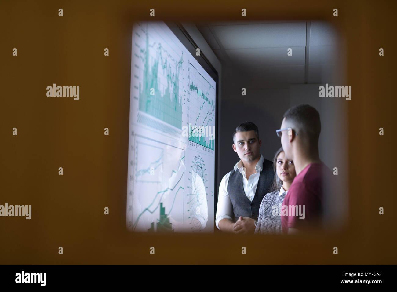 Business team in meeting seen through glass door - Stock Image