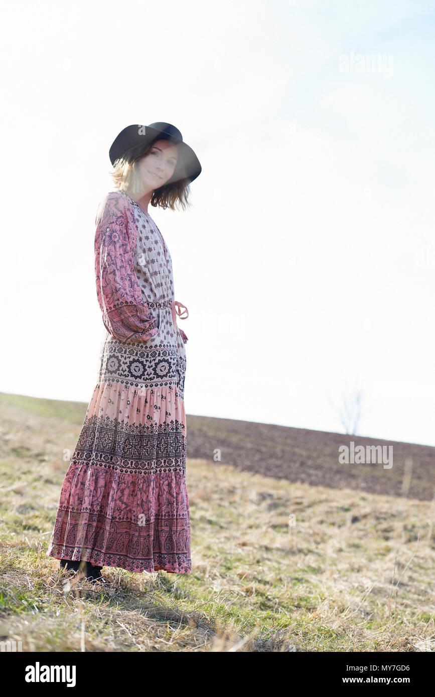b345b93d5e0 Hippy style woman wearing felt hat in field