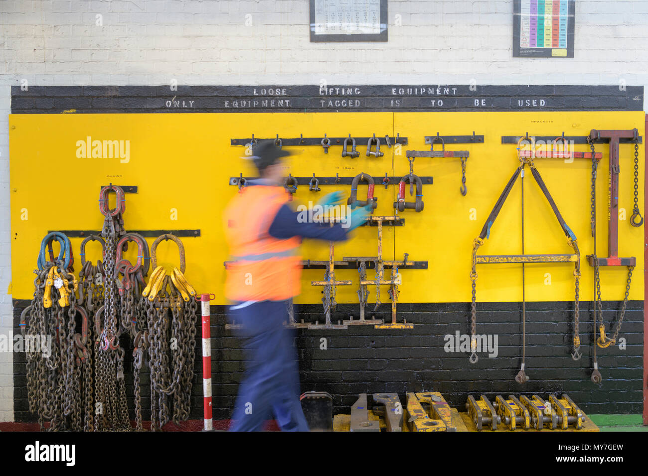 Engineer selecting lifting equipment in train engineering factory - Stock Image