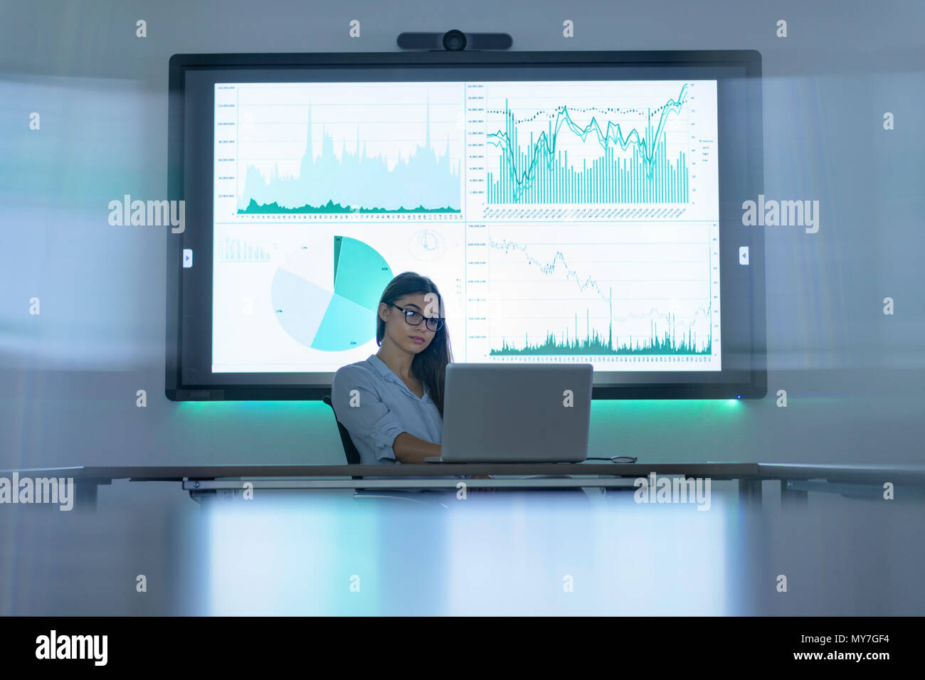 Businesswoman using laptop and interactive screens with charts and graphs in business meeting - Stock Image