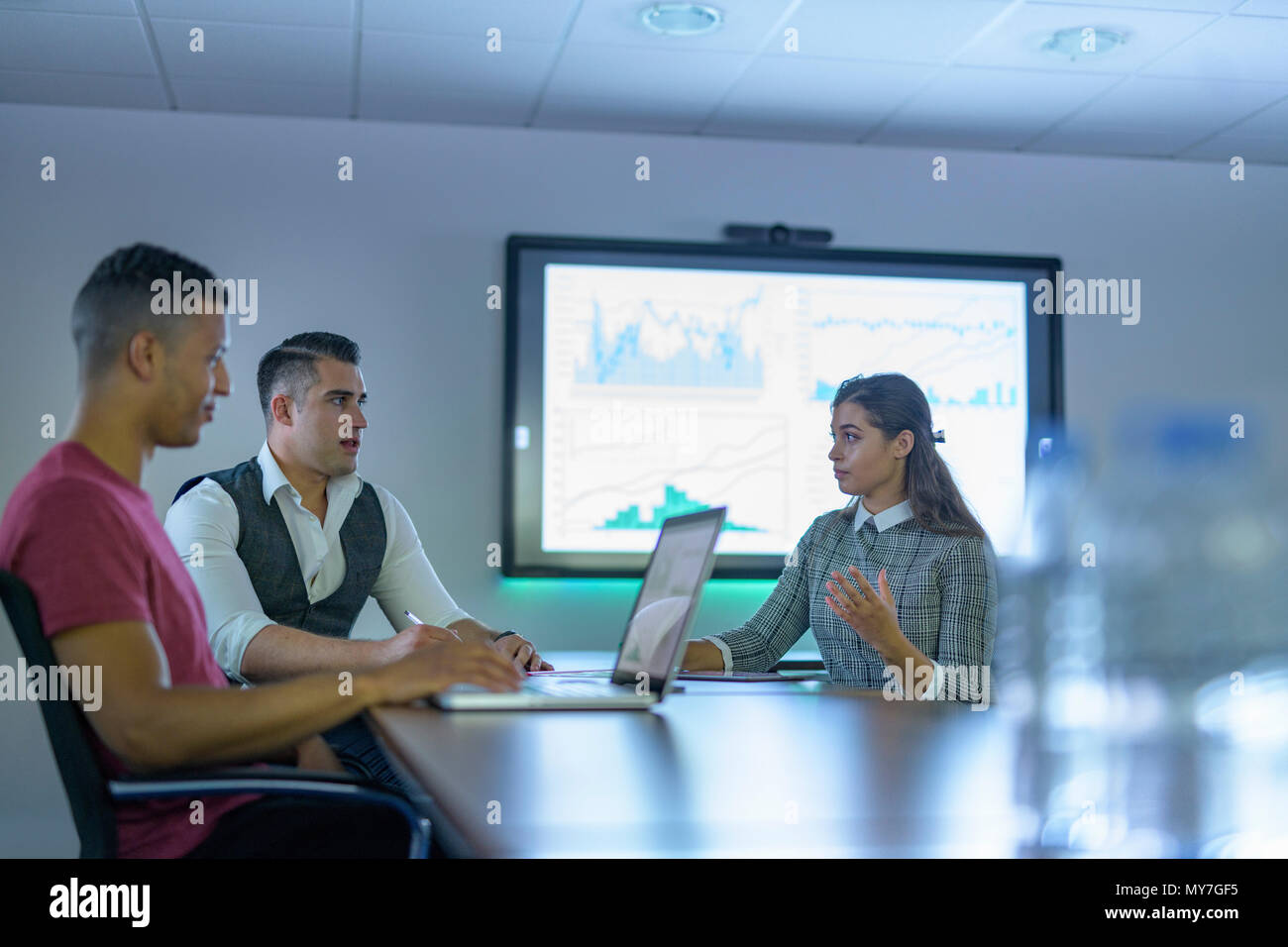 Business team using laptop and interactive screens with charts and graphs in business meeting - Stock Image