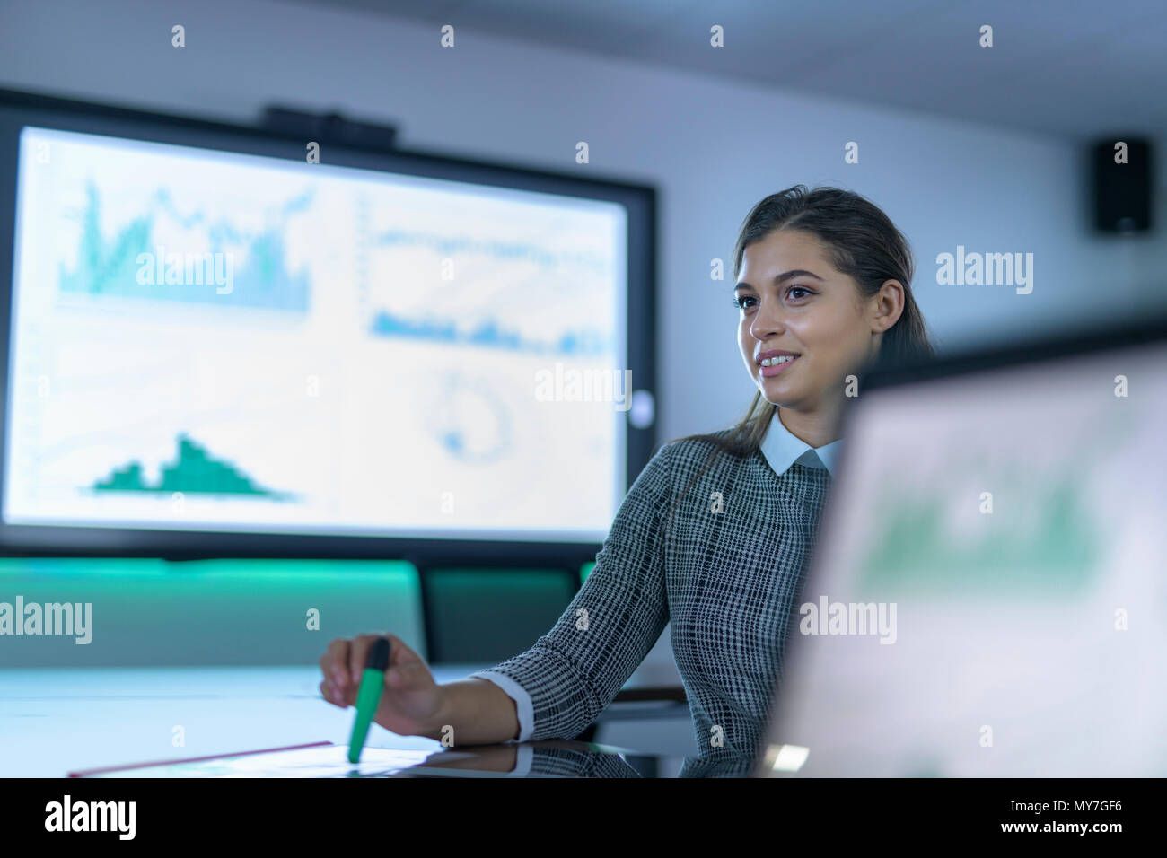 Portrait of businesswoman using laptop and interactive screens with charts and graphs in business meeting - Stock Image