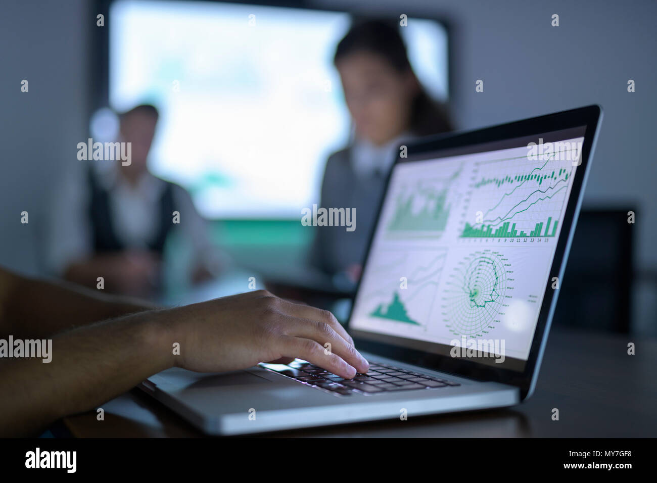 Businessman viewing charts and graphs on laptop in business meeting, close up - Stock Image