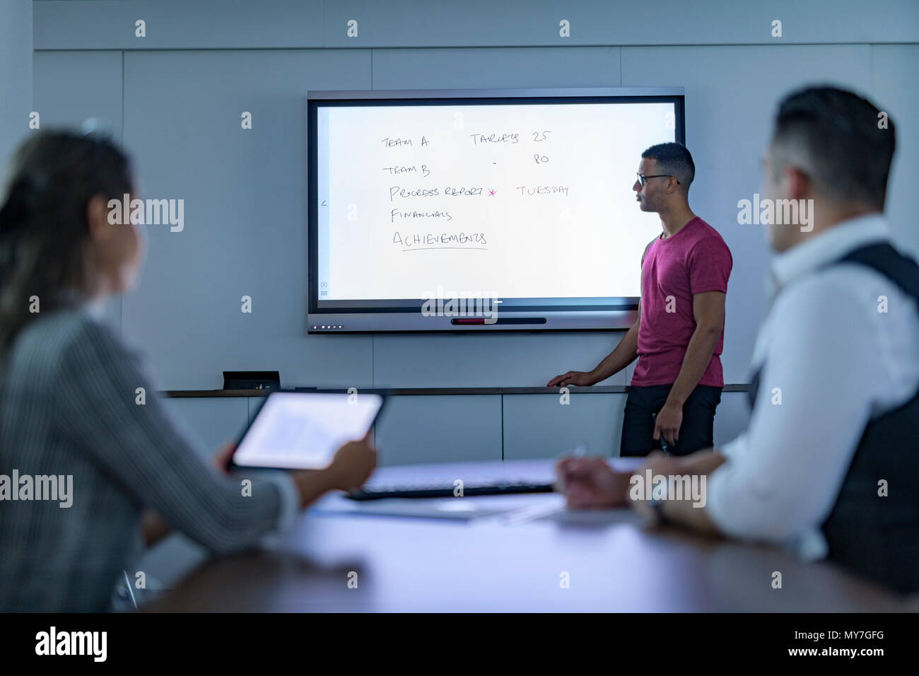 Businessman writing on interactive screen in business meeting - Stock Image