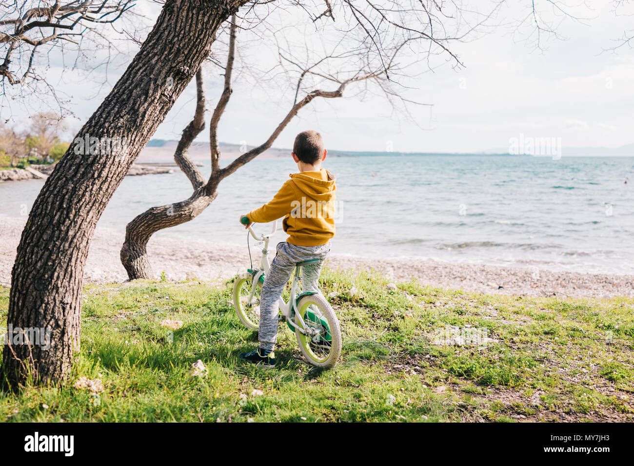 6 years old boy sitting on his bike by the sea - Stock Image