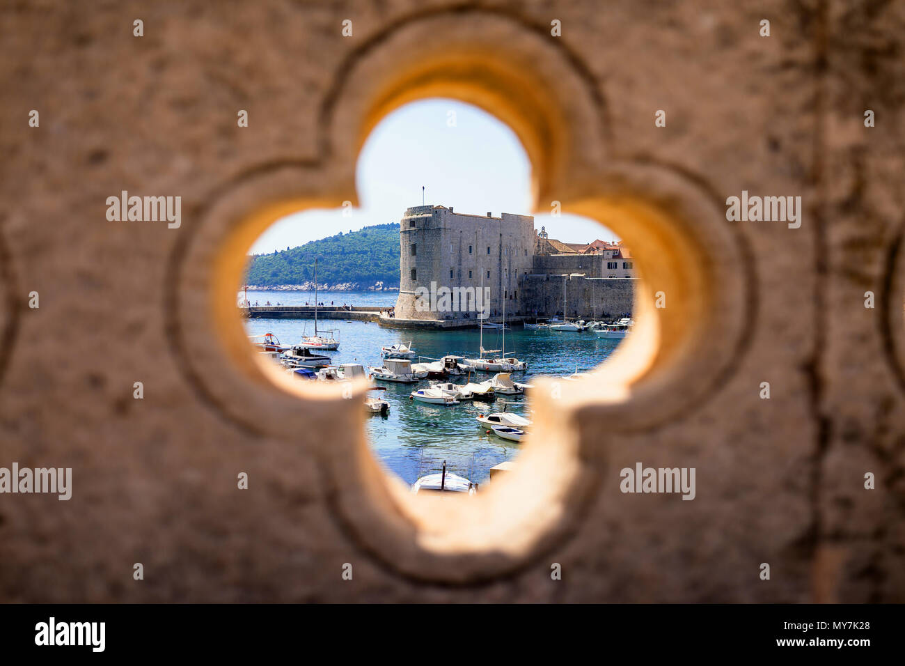 Dubrovnik harbor view through stone carved detail - Stock Image