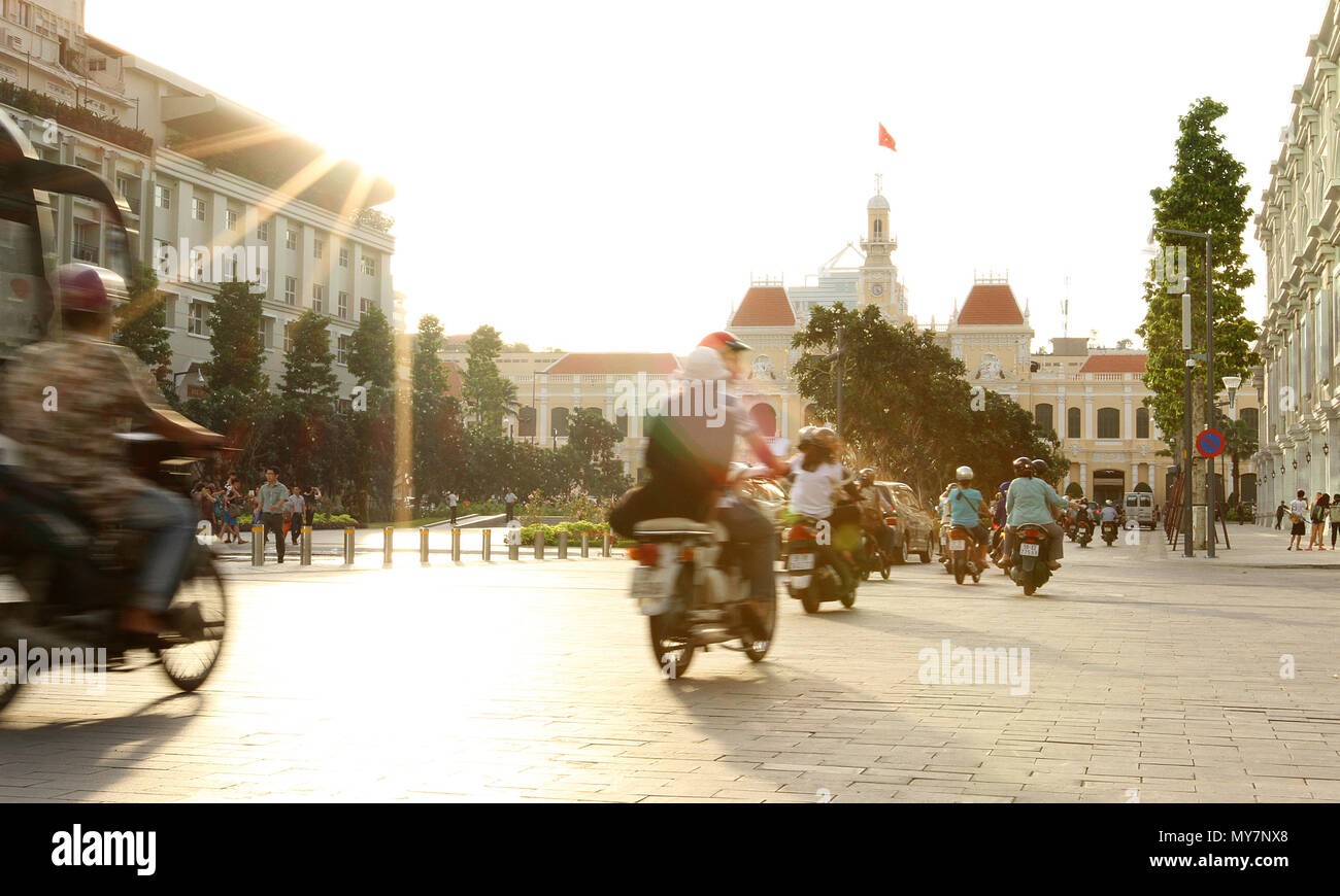 View to Ho Chi Minh city town hall on sunset with motorbikes moving and Vietnamese flag flying. Tourist travel holiday guide concept. Vietnam - Stock Image