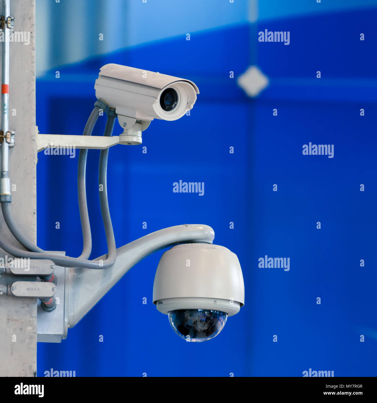 CCTV camera or surveillance operating on blue wall bakcground - Stock Image