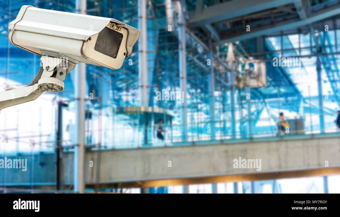CCTV camera or surveillance operating with electric door in background - Stock Image