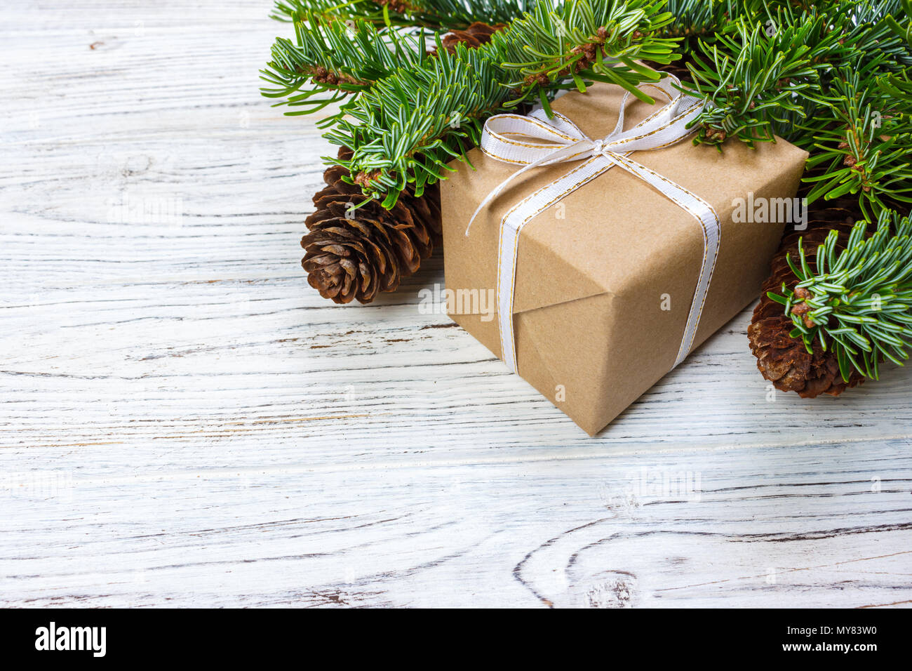 Christmas gift box on the white wooden table background,spruce branch,pine cones,frame,top view,space for text. - Stock Image