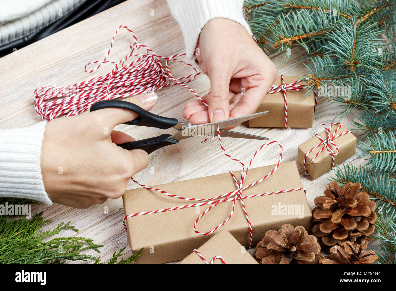 Christmas gift wrapping background. Female hands packaging christmas present with red ribbon, top view. Winter holidays concept, flat lay. Woman holdi - Stock Image