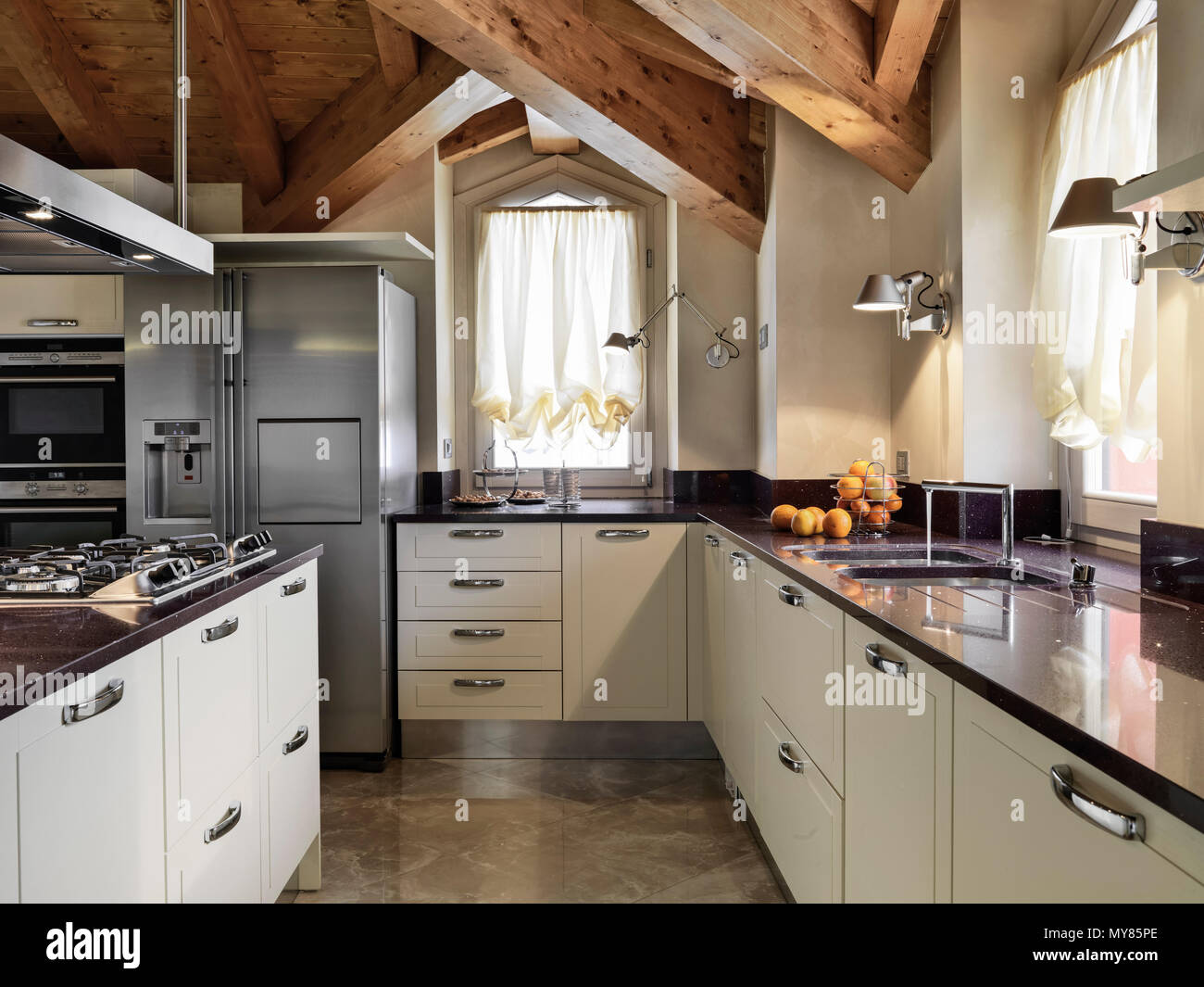 modern kitchen interior in the attic room with kitchen island and wooden ceiling - Stock Image