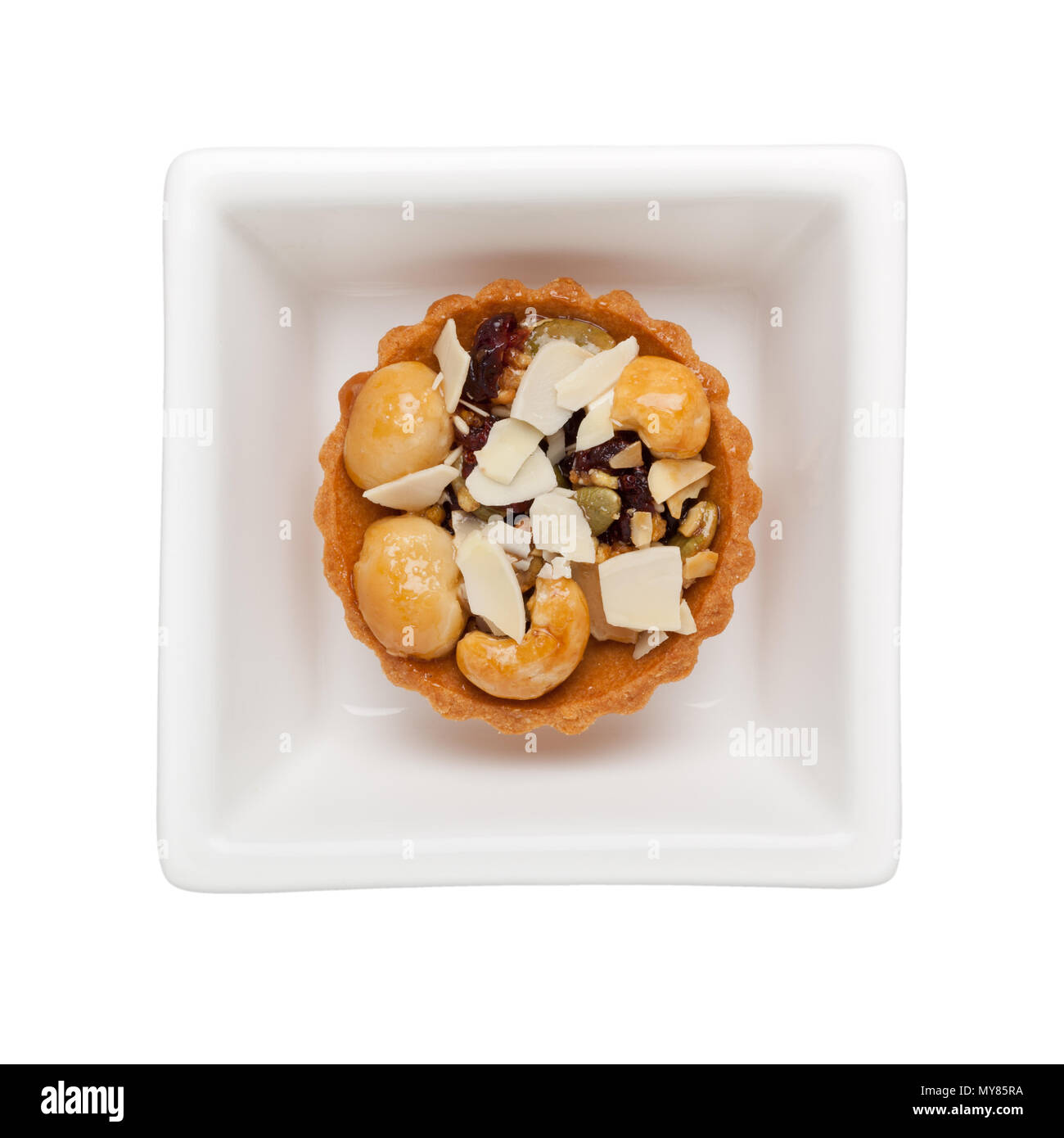 Mixed nuts tart in a square bowl isolated on white background - Stock Image