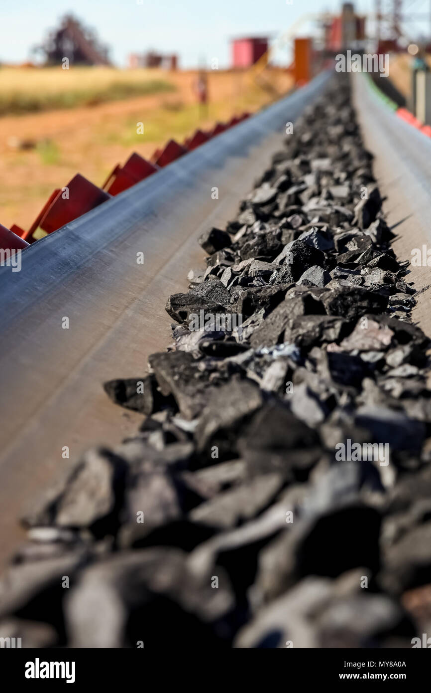 Close up of Manganese rock being moved on a conveyor belt - Stock Image
