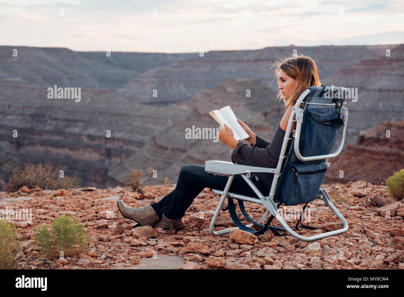 Young woman in remote setting, sitting on camping chair, reading book, Mexican Hat, Utah, USA - Stock Image