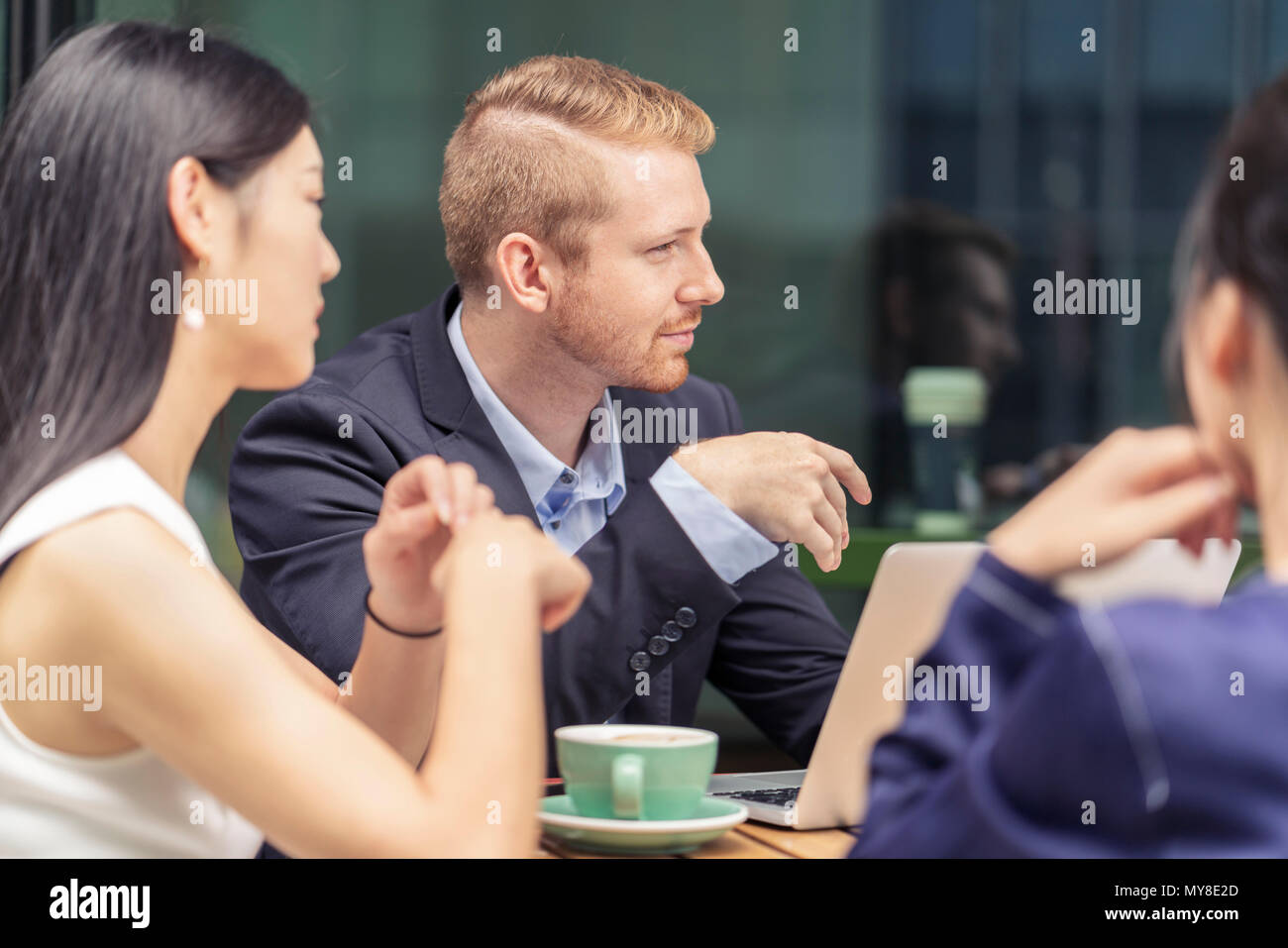 Group of businesspeople, having meeting at cafe, outdoors - Stock Image