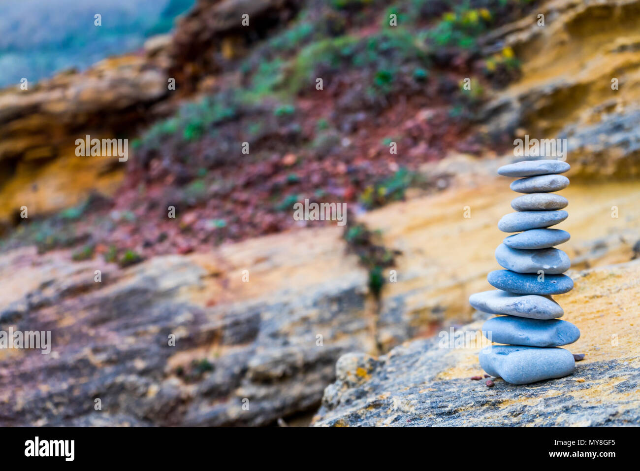 Flat stones stacked on each other zen-like in front of a colorful blurry backdrop - Stock Image