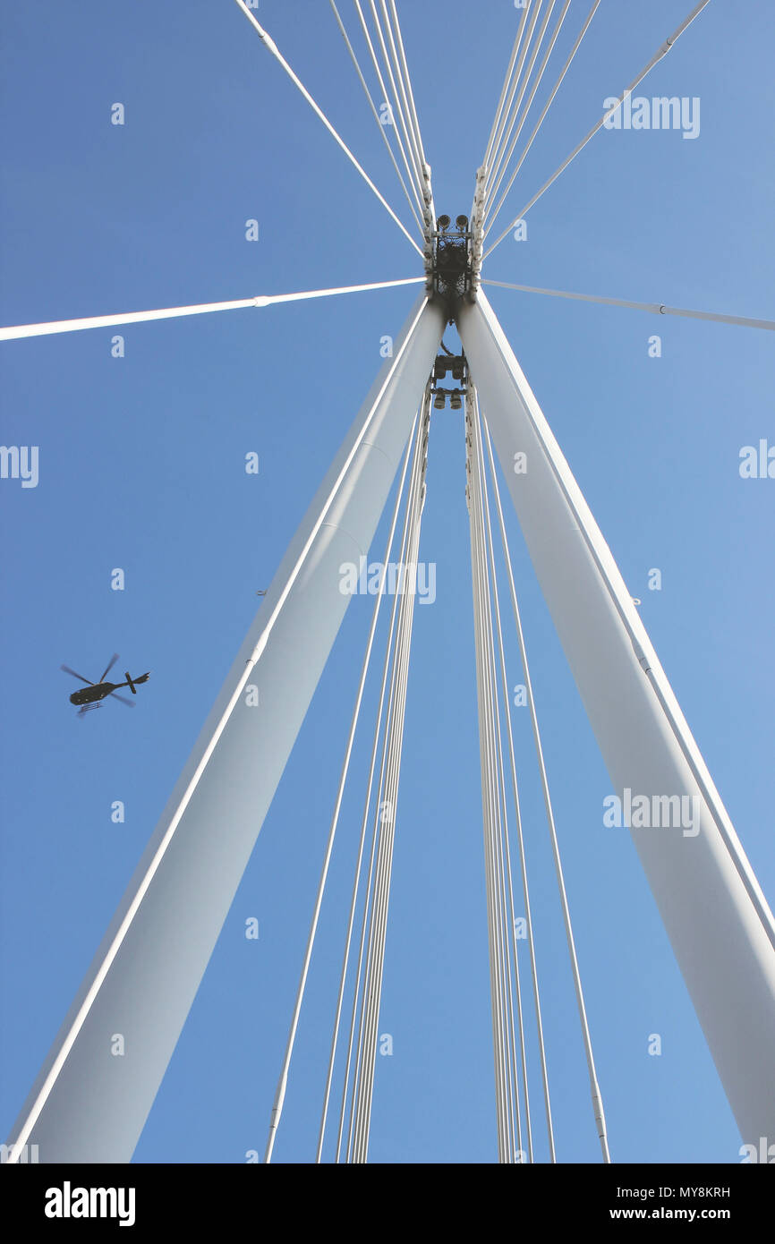 A helicopter flies over Hungerford Bridge in London. - Stock Image