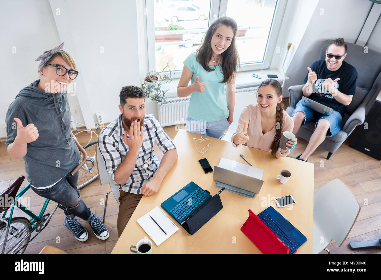 Young cheerful people showing thumbs up for co-working - Stock Image