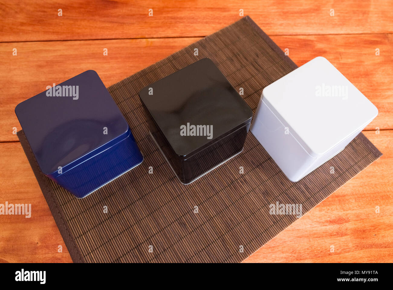 Three colorful metal boxes stand on a bamboo napkin,view from above - Stock Image