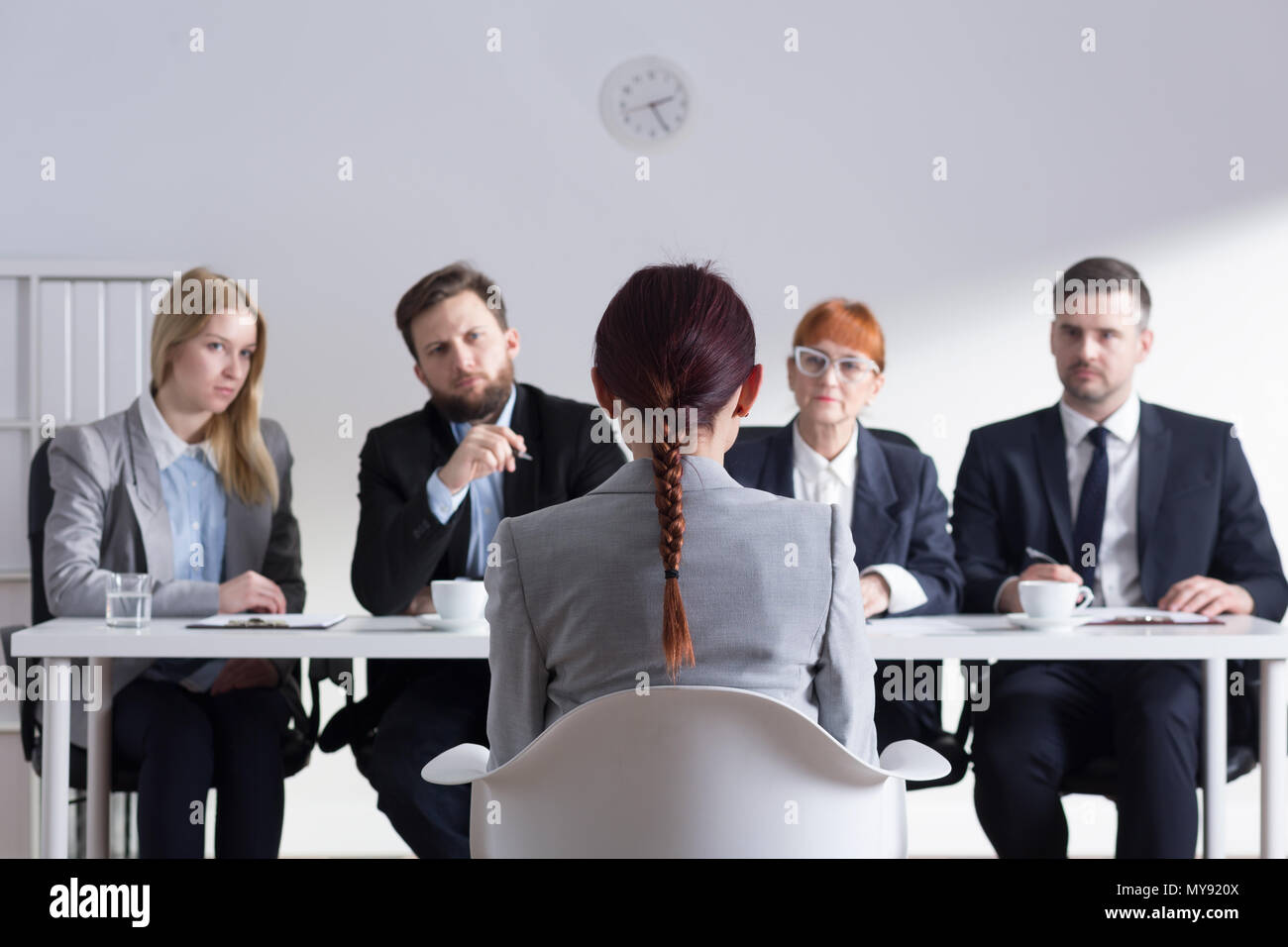 Woman during job interview and four elegant members of management - Stock Image
