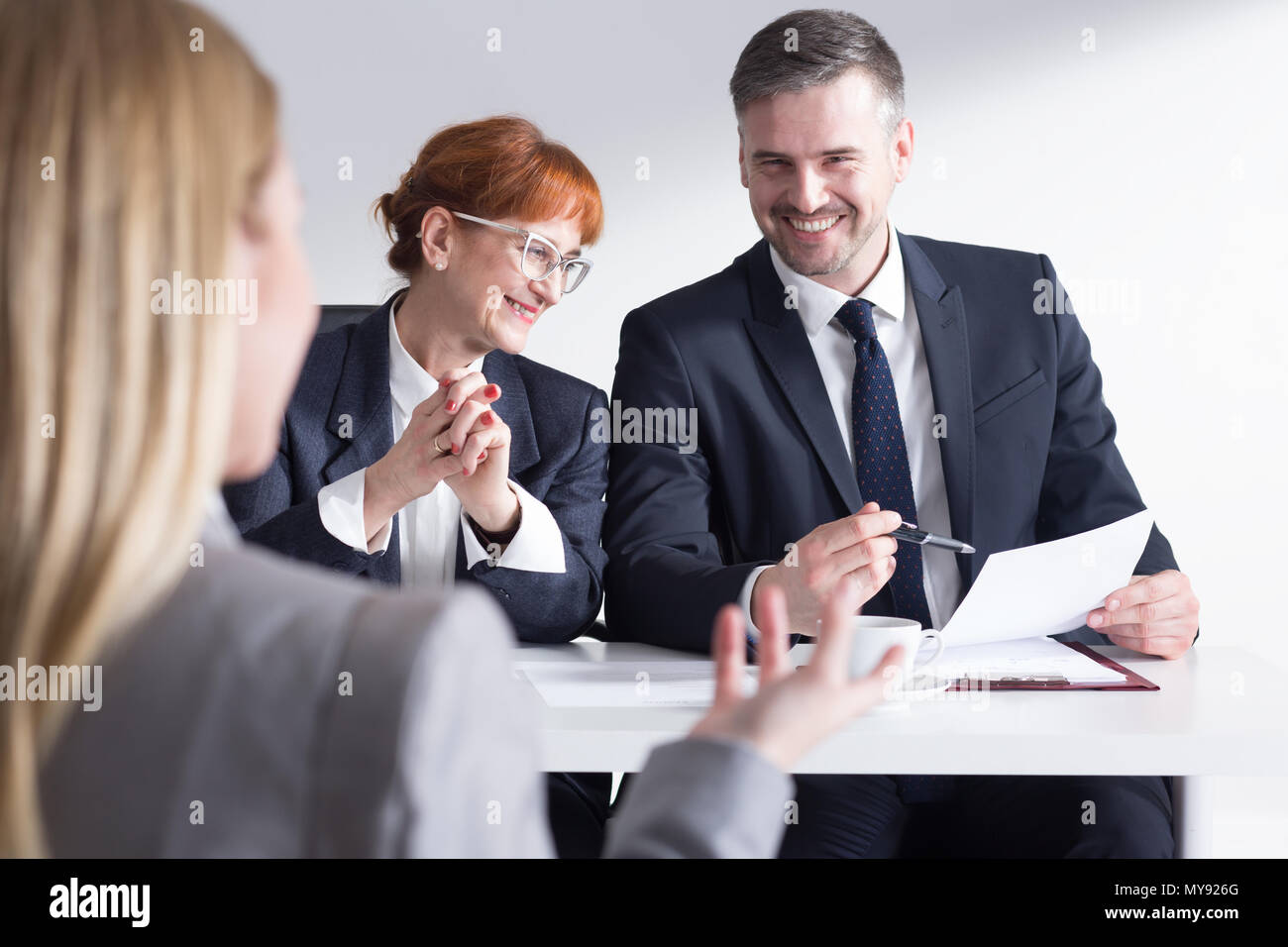 Job applicant back view and two elegant corporate workers - Stock Image