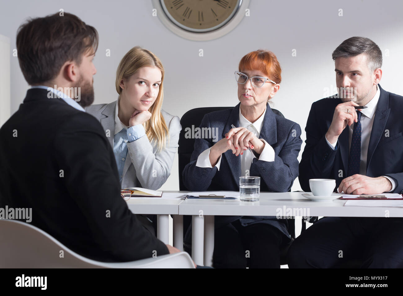 Man back view during job interview and three businesspeople sitting beside table - Stock Image