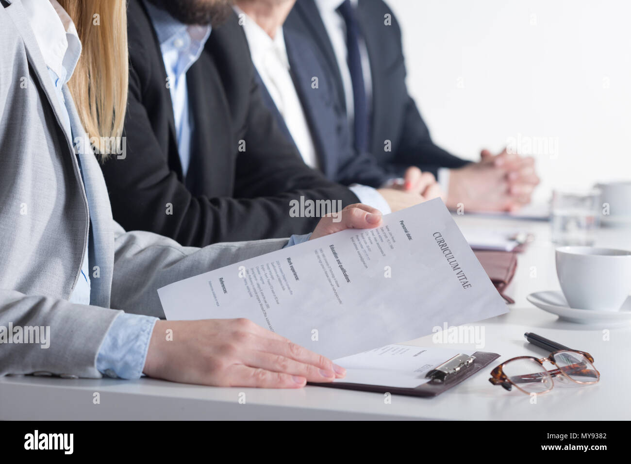 Woman holding CV sittting next to three businesspeople beside table - Stock Image