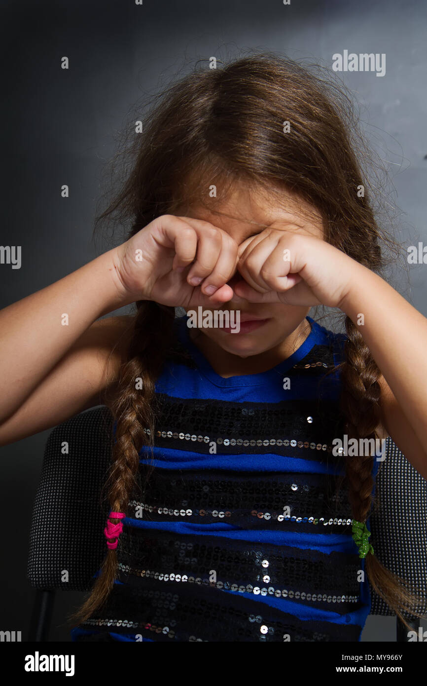 a little girl with two pigtails sits and weeps bitterly on a grubby gray background - Stock Image