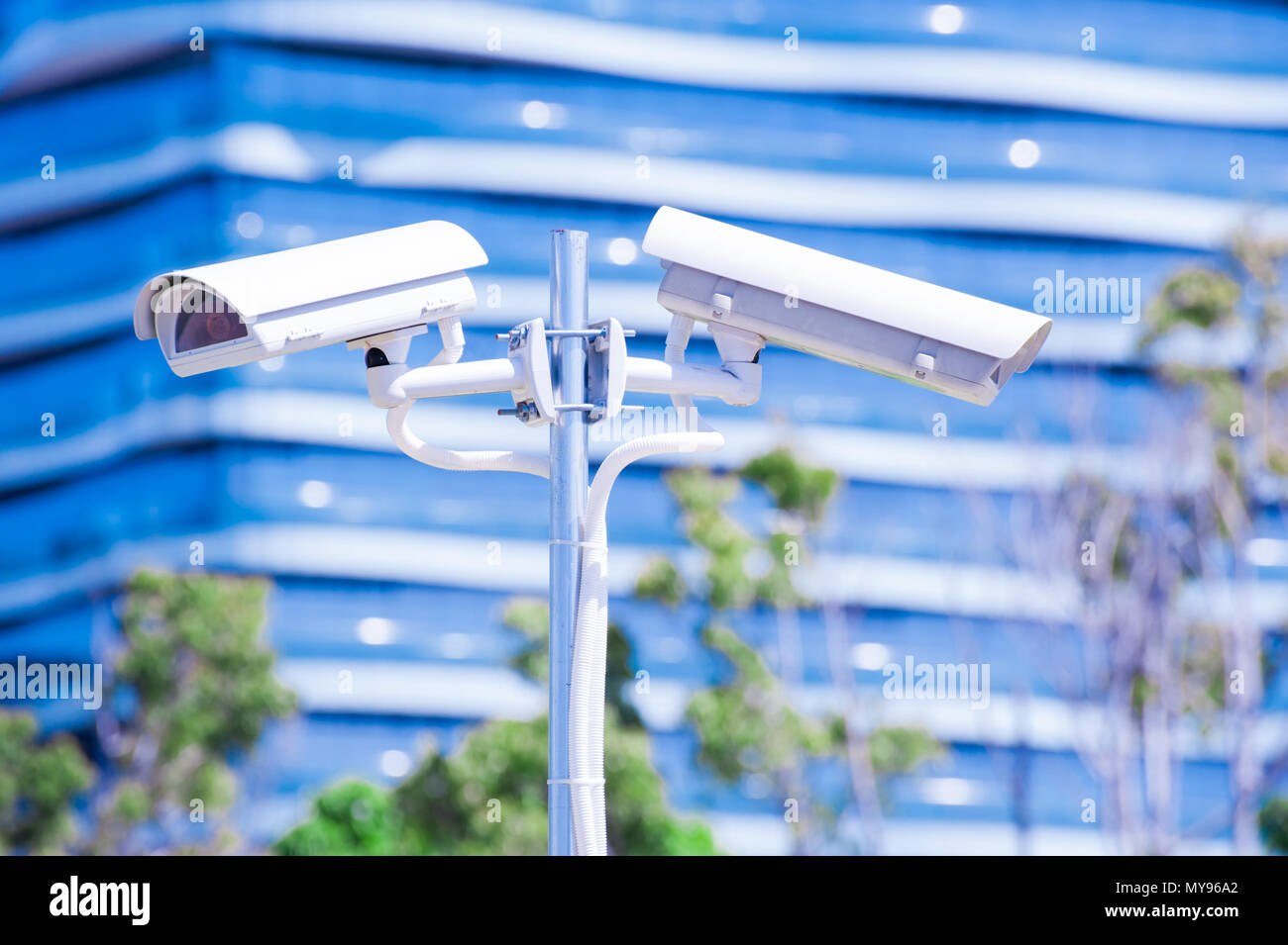 CCTV camera or surveillance operaiting with blue building in background - Stock Image