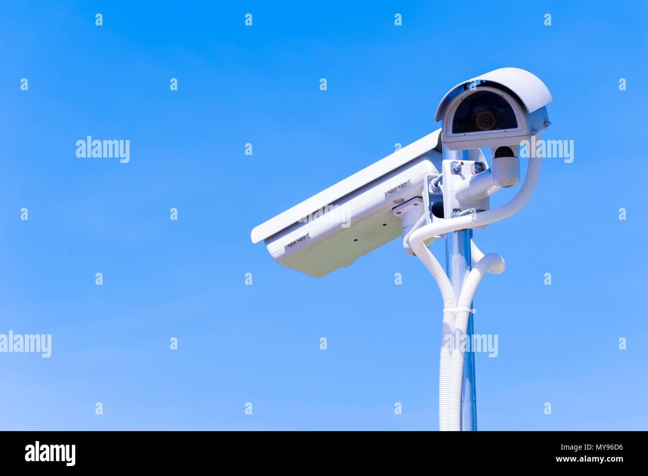 CCTV camera or surveillance operaiting on blue sky - Stock Image
