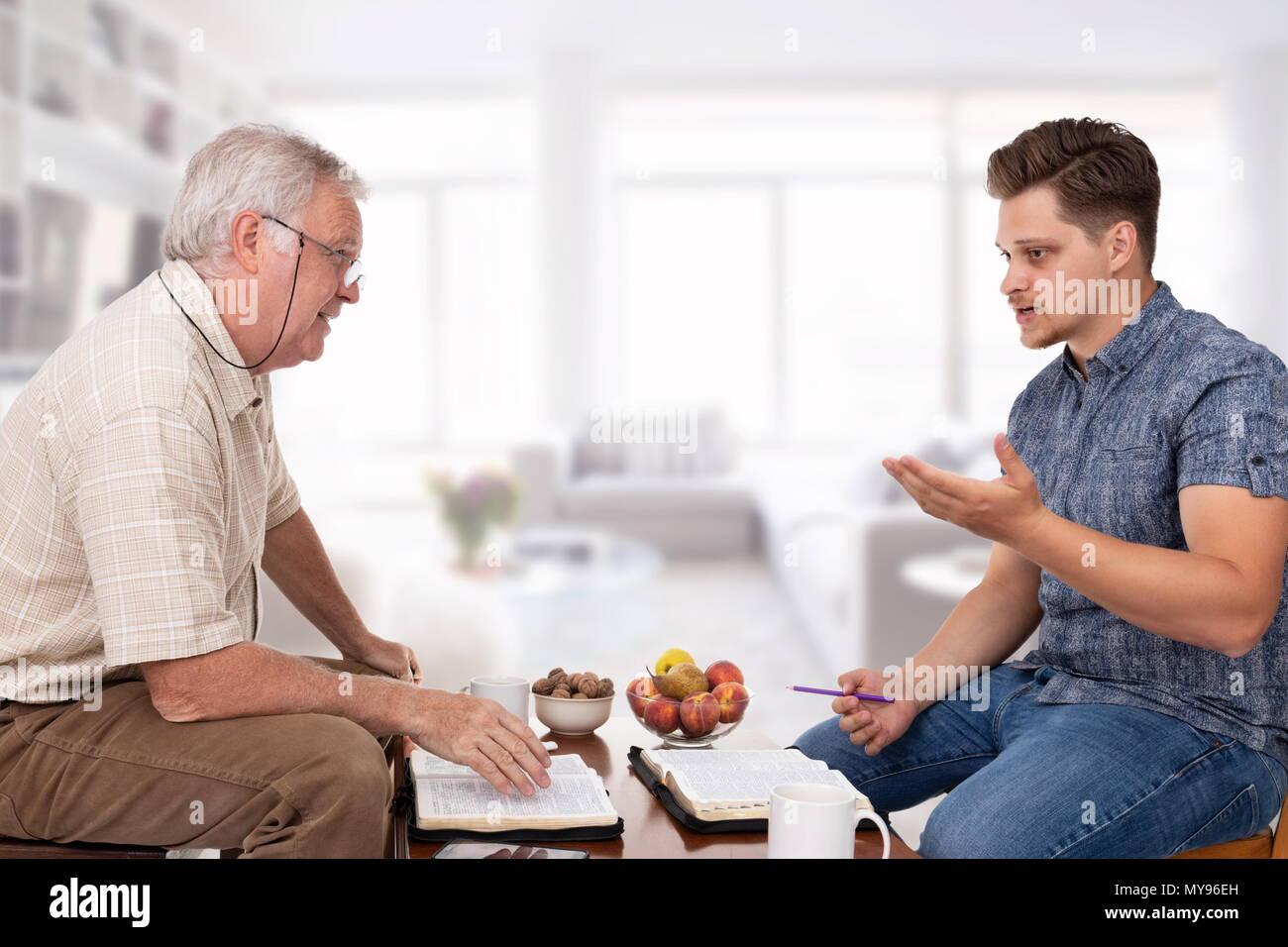 Church servant counselor doing spiritual counseling to a young man studying the Bible - Stock Image