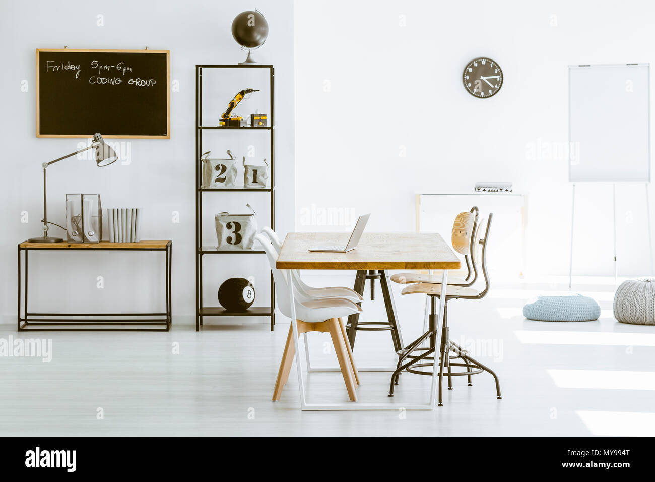 Bright classroom with laptop on desk and blackboard on the wall - Stock Image