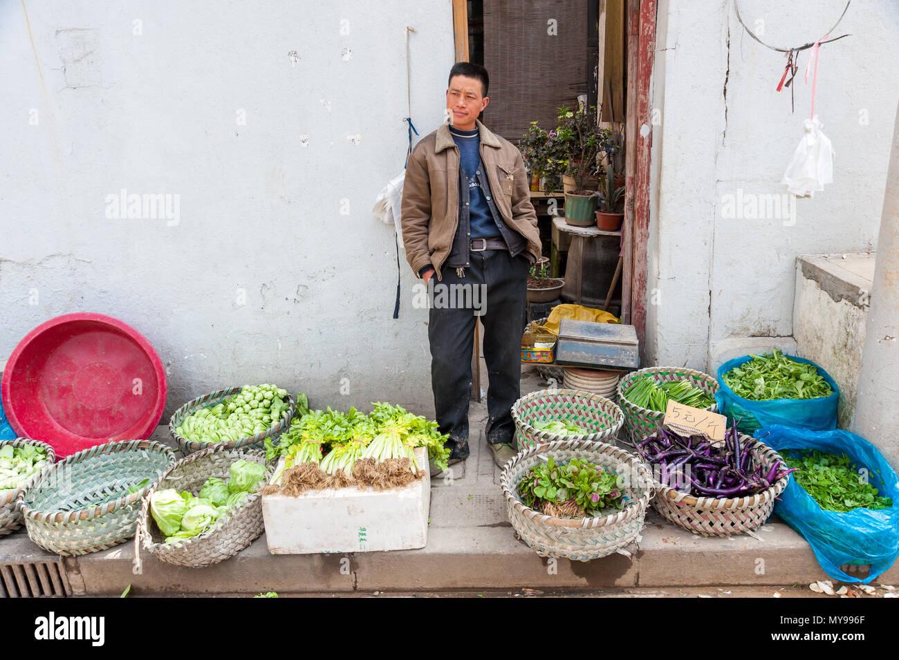 Man selling fresh produce from countryside at market stall on Dajing Road Market, Shanghai, China - Stock Image