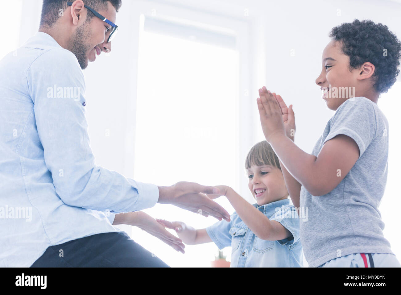 Happy children play clapping hands with teacher at his home - Stock Image