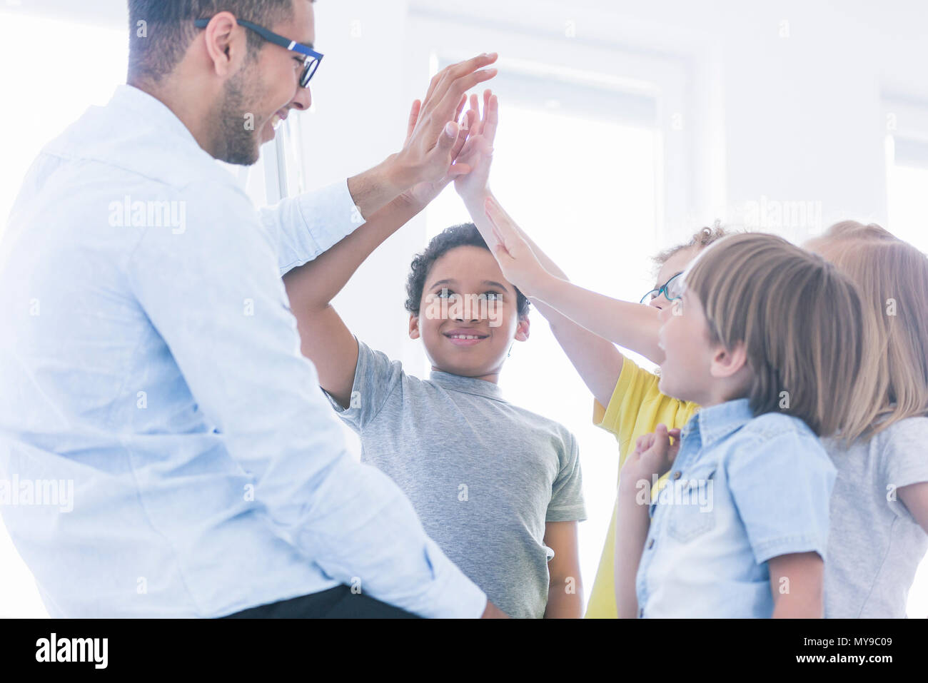 Students have fun with teacher during information technology classes - Stock Image