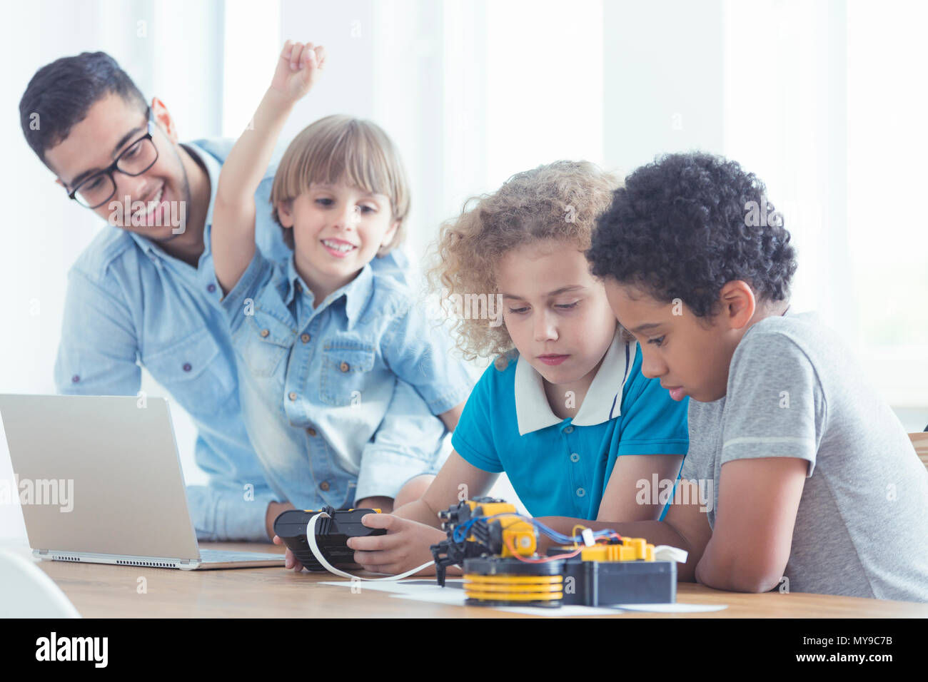 Children and teacher play with robots during modern computer classes - Stock Image