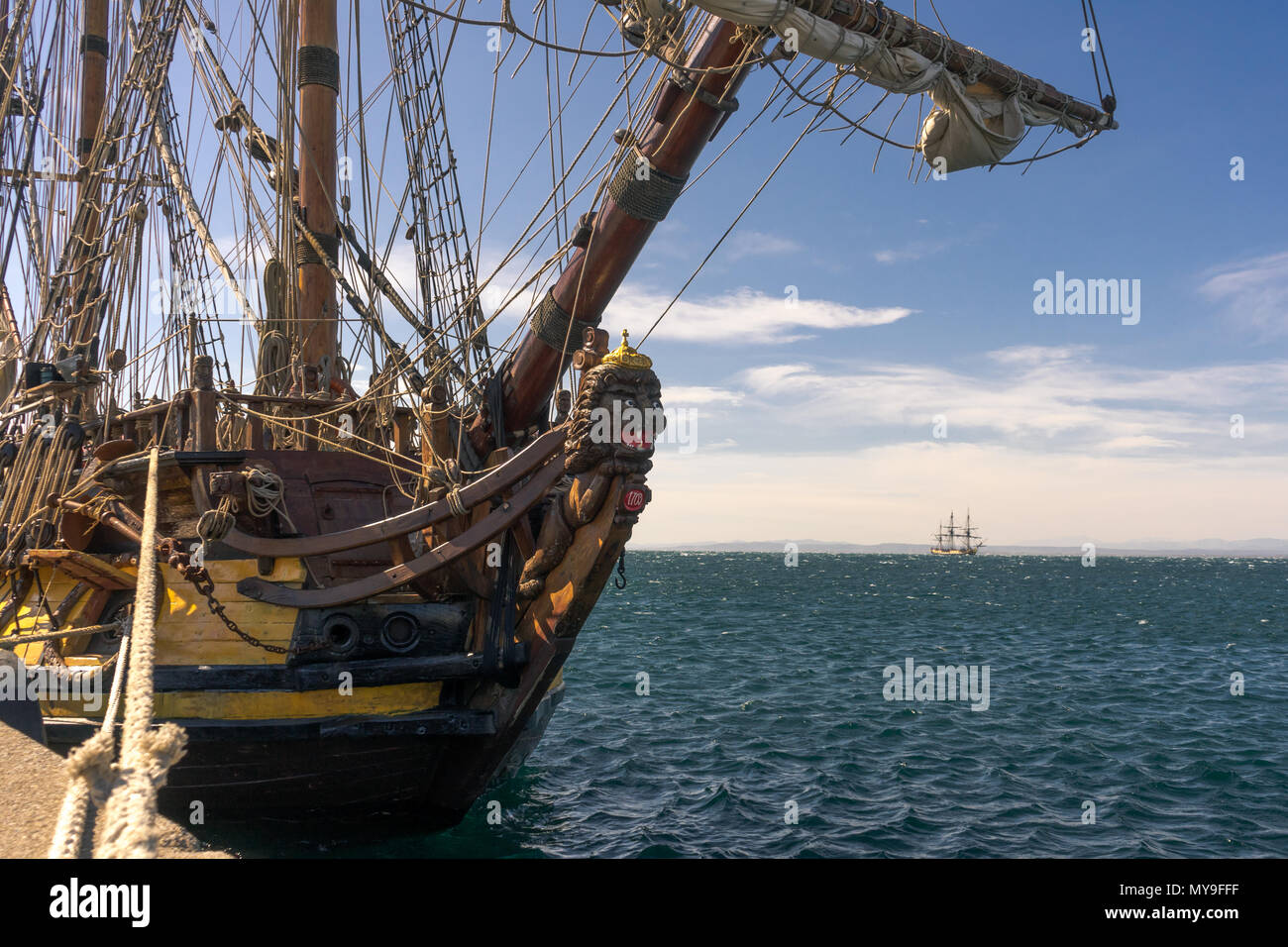 Old sailboat from 1703 anchored at shore with another ship waiting in the background - Stock Image