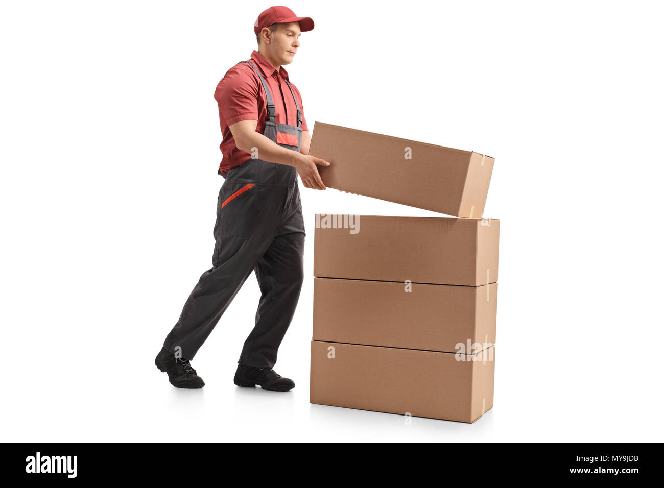 Full length profile shot of a mover placing a package on top of a stack isolated on white background - Stock Image