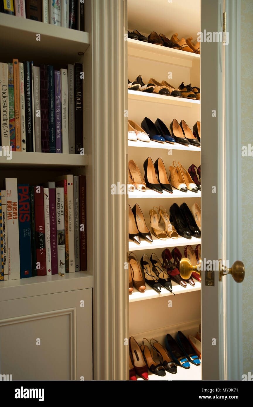 High heels in wardrobe by bookcase - Stock Image