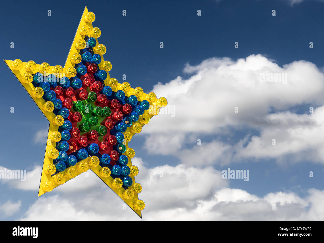 Large colorful star of differently colored lamps exempted in front of a blue sky with clouds, illustration - Stock Image