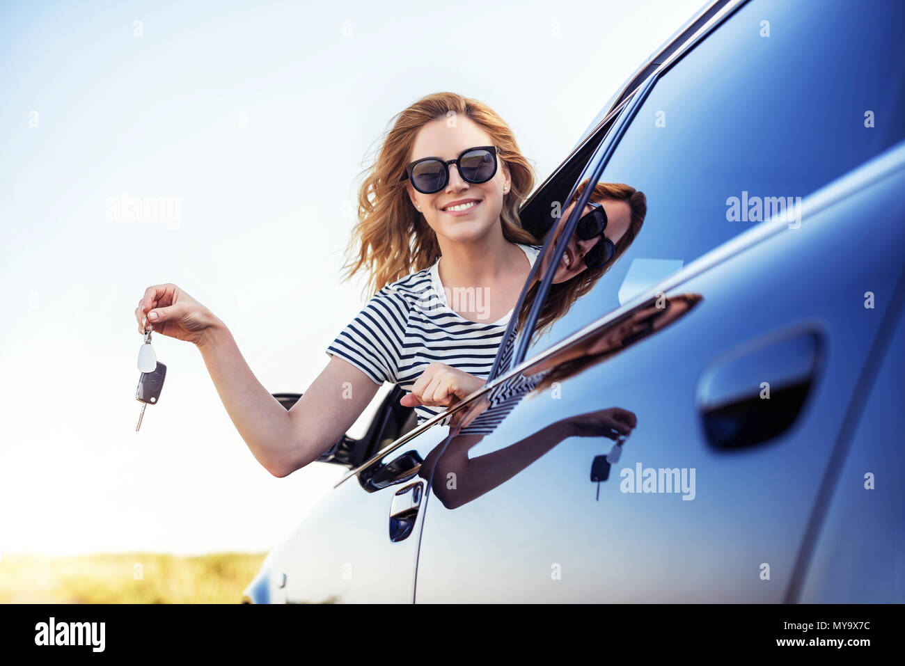An Attractive Woman In A Car Holds A Car Key In Her Hand Rent Or