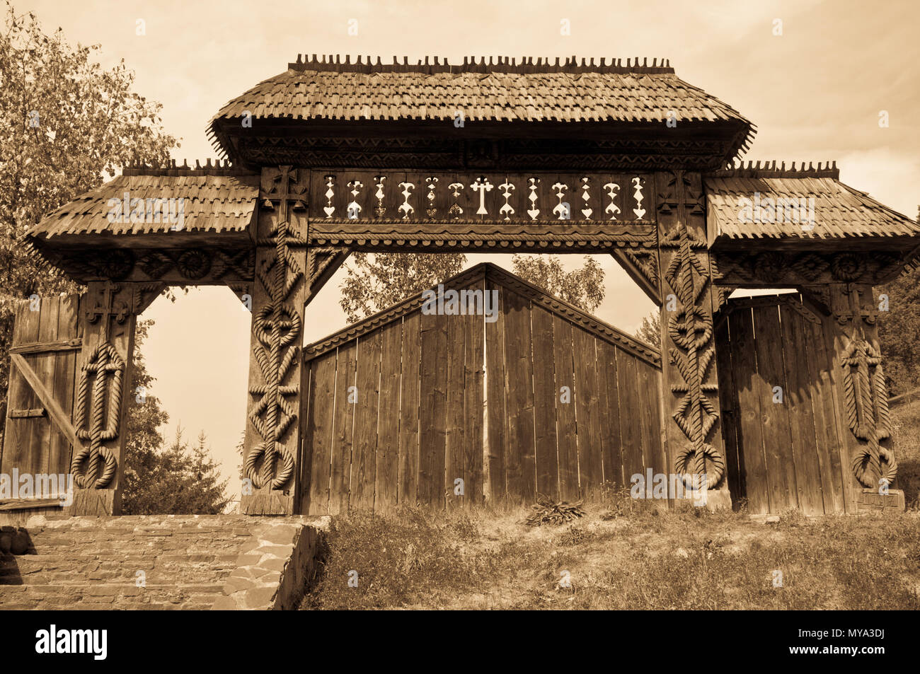 Traditional carved wooden gate from Maramures region, Romania, sepia tones. - Stock Image
