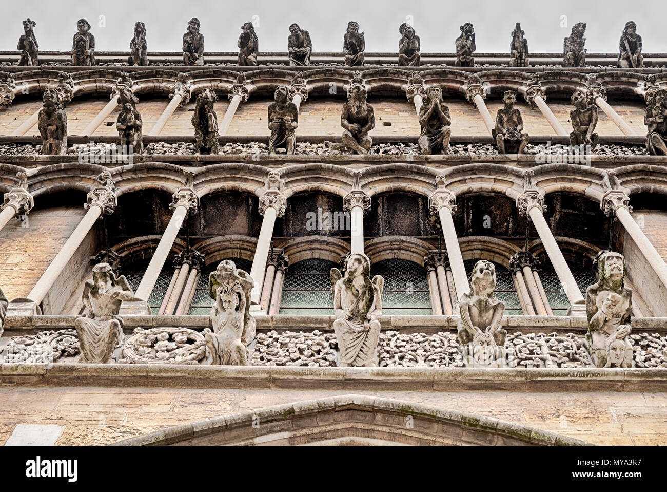 The front facade of the Notre Dame cathedral in Dijon, France, is lined with different gargoyles looking out over the city. - Stock Image